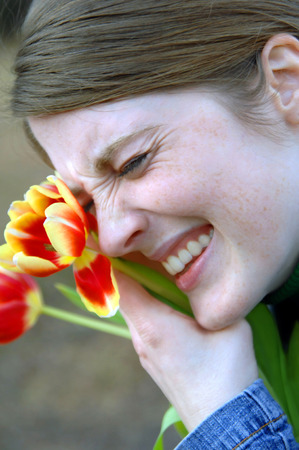 beaming: Spring is finally here.  Teen joyfully hugs the first blooming tulips up to her face and laughs with joy.