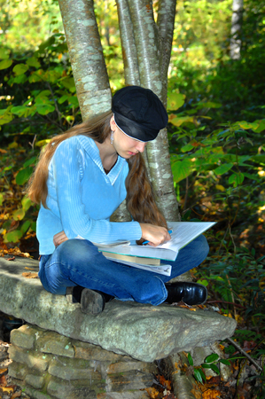 Young teen sits on a bench outdoors and concentrates on the book she is studying.  She is wearing a sweater and jeans.  She has a hat on her head.