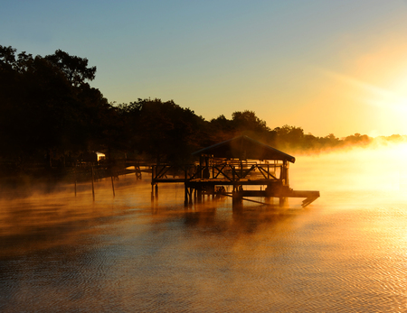 boat house: Golden light tints water and wooden dock gold, as the sunrise hits Lake Chicot in Eastern Arkansas.  Fog surrounds boat house and surface of lake. Stock Photo
