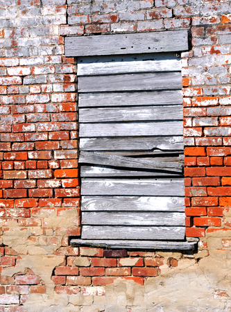boarded: Background image shows an old brick building smeared with mortar.  Lone window is boarded up with white washed and weathered boards.