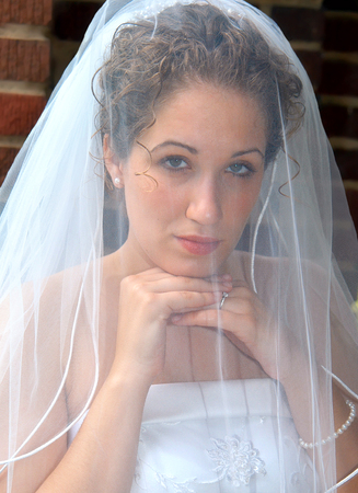 solemn: Beautiful bride bows her head onto her hands and is solemn as she looks through her veil.