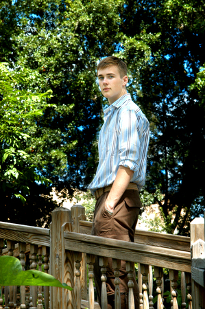 solemn: Handsome young teen poses on a rustic wooden bridge in Louisiana.  He is solemn and thoughtful.