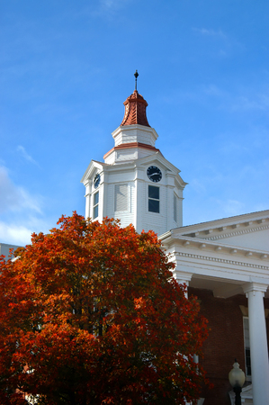 County courthouse in North Arkansas has copper top, brick and white wooden construction.  Autumn foliage covers tree by courthouse with brilliant orange.
