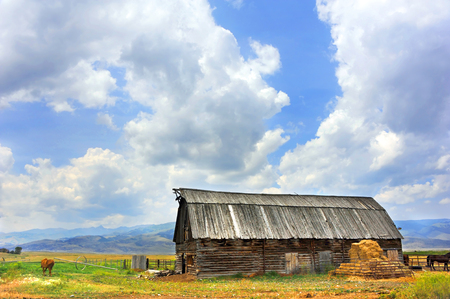 Rustic, wooden, log barn has beautiful mountain view in Happy Valley, Montana.  Barn has wooden roof. Reklamní fotografie - 72102473