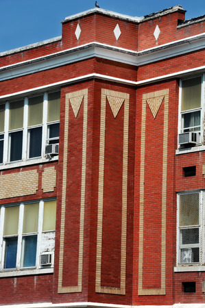 Unusual design decorates corner of Lincoln School in Livingston, Montana.  Blond colored brick sets pattern in red brick of building.