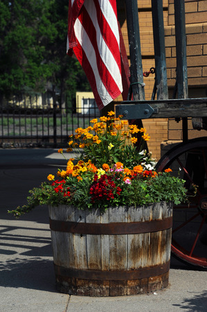 Old, wooden barrel serves as a planter for beautiful flowers.  Barrel sits in front of the Old Train Depot in Livingston, Montana.