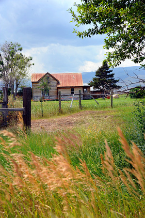 Wood frame homestead is tin roofed, and peeling paint.  Fence fronts home and tall grass blows in the wind. Stock Photo