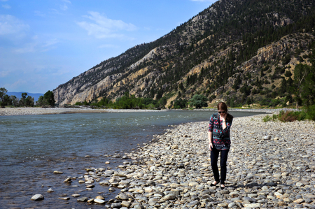 Young woman wanders the beach access site at Carters Bridge near Livingston, Montana.  River disappears around a curve at base of mountain.