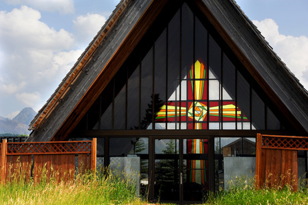 enhances: Beautiful stained glass cross enhances view from this memorial garden chapel.  View is of the Absaroka Mountains.
