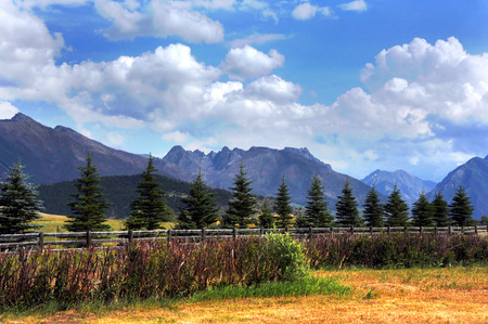 Rustic, wooden fence runs across photo, seperating field from distant, Absaroka mountains in Montana.  Blue sky and fluffy clouds complete image. Banco de Imagens - 72446690
