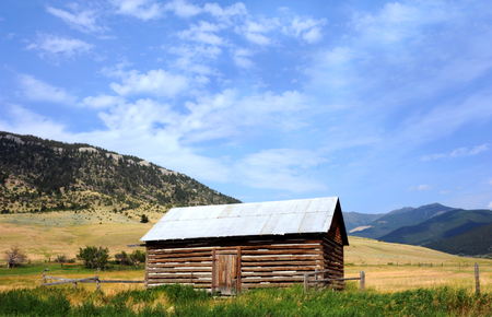 Small log cabin, with tin roof, sits in a field at the foothills of the Absaroka Mountains in Montana.