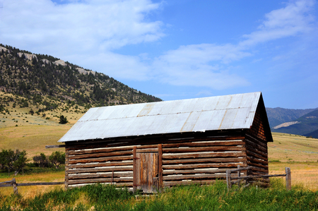 Rustic log cabin, with tin roof, has beautiful backdrop of the Absaroka Mountains in Montana.  Cabin has front door, tin roof and wooden fence.