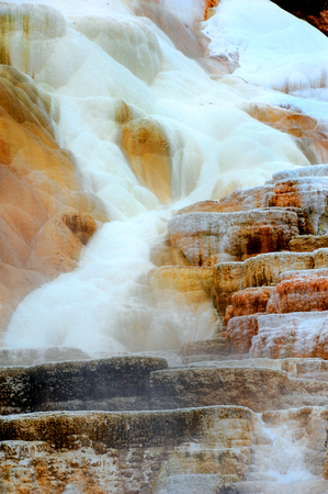 Travertine deposits mix with steam from the hot springs of Mammoth Springs in Yellowstone National Park. Stock Photo