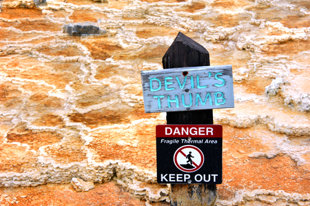 identifies: Sign identifies Devils Thumb and also warns visitors to Yellowstone National Park of the danger of the thermal area.  Sign is wooden with aqua lettering.