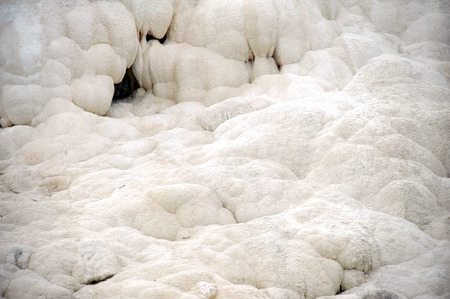 White travertine terrace is covered in white deposits at Mammoth Springs in Yellowstone National Park.