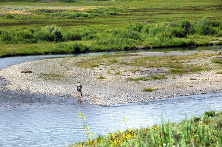 Lone fisherman walks along a rocky shoal in the middle of Soda Butte creek in Yellowstone National Park. Stock Photo