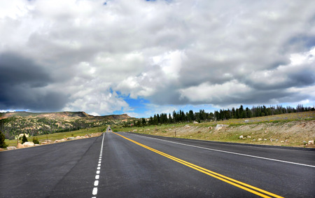 Blacktop highway disappears into the mountains of Beartooth Pass Scenic Byway.  Stormy clouds threaten blue sky over mountains.