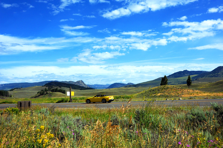 blacktop: Yellow convertible travels the a highway through Lamar Valley in Yellowstone National Park.