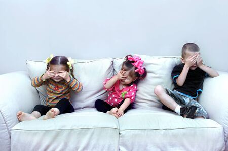 Three small children, sit on a couch in their home, and pretend to see no evil.  They have their hands over their eyes. photo