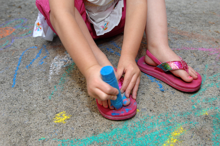 Little girl creatively paints her toe nails with blue sidewalk chalk. photo