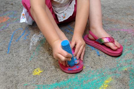 Meisje schildert haar teennauwen creatief met blauw trottoirkrijt. Stockfoto