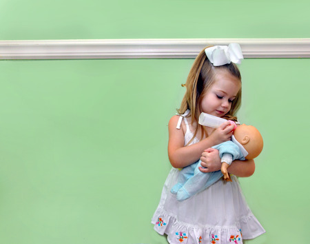 cradling: Little girl pretends to be a mother, as she holds her doll and gives her a bottle.  She is standing in front of a green wall in her home. Stock Photo