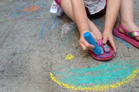 彼女のつま先の釘をいくつかの歩道の助けを借りて、青い少女塗料チョーク showiing 創造性と、ボックスの外側を考える。 写真素材