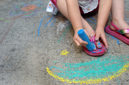Little girl paints her toe nails blue with the help of some sidewalk chalk showiing creativity and thinking outside the box. photo