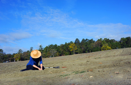 Woman, wearing a straw hat, sits in the dirt field at Crater of Diamonds State Park in Murfreesboro, Arkansas.  She is digging for diamonds. Фото со стока