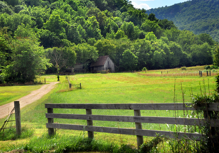Landscape image of old barn surrounded by Arkansas mountains and trees.  Barn is wooden, weathered and has a rusty tin roof.  Gravel road enters farm. Фото со стока
