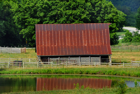Arkansas Ozarks surround this old wood barn.  Barn is wooden, weathered and has a rusty tin roof.  Reflection is seen in the pond that is next to barn.