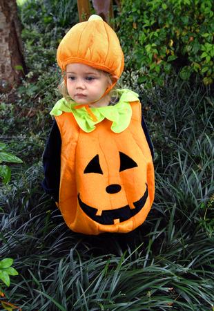Klein meisje, gekleed in een pompoen kostuum, compleet met hoed, staat buiten in het hoge gras. Ze denkt aan de griezelige Halloween komen.