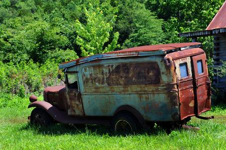 アーカンソー州のオザークの放棄された小屋の他に、錆びて壊れた古いジャロピーが座っています。 「ヒルビリー」と書かれたトラックの看板はほ