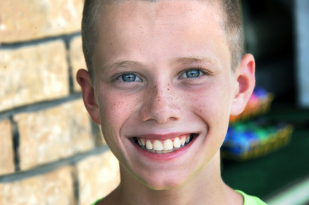 Young boy grins as he begins a round of put-put golf.  Closeup shows he has a sprinkle of freckles across his nose and cheeks.