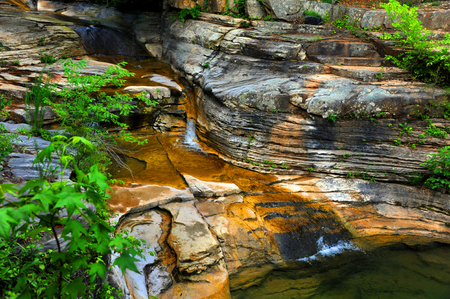 Stream falls in cascades over rocky ledges in the Arkansas Ozark Mountains.   Stock Photo