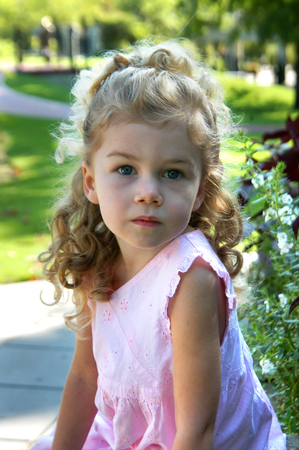 Angelic little girl looks into the camera.  She is thinking and looking off into the distance.  She has blond hair and ringlets.