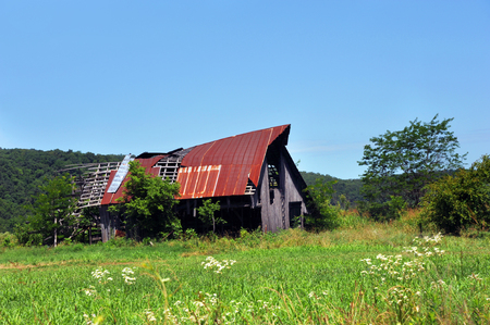 Arkansas barn, in the Ozark Mountains, is broken and dilapidated.  Tin is torn away from roof by wind.