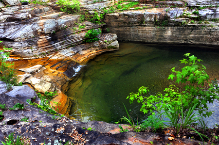 Hidden pool has calm and still surface.  Water trickles in from a small cascade on the rocky ledges.  Pool is located in the Arkansas Ozark Mountains. Stock Photo