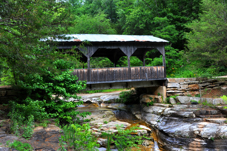 Wooden covered bridge spans small creek in the Ozark Mountains of Arkansas.  Pool bubbles over rocky ledges. Stock Photo