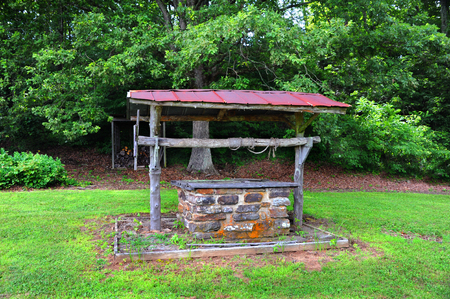 Old fashioned water well is covered and abandoned.  Frayed rope is wound around log ar across tope of well.  Well is in Northern Arkansas.