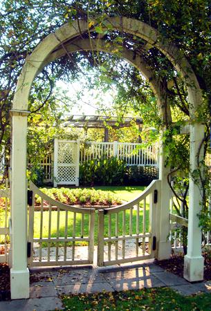 Garden gate has swinging gates and sunshine.  Arches from gate post in the Birmingham Botanical Garden in Birmingham, Alabama.