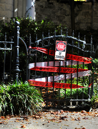 Black iron gate is wrapped with caution tape that says do not enter.  A metal sign hanging from the gate reads Beware of Zombies. 写真素材