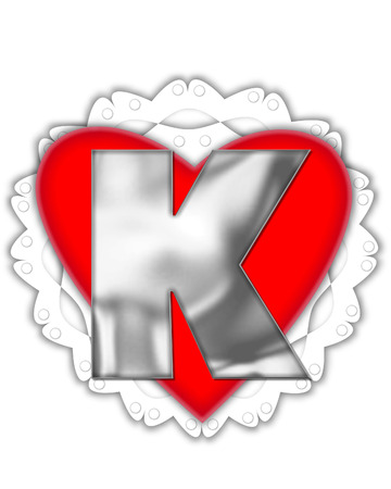 The letter K in the alphabet set Valentine Foil, is metalic silver.  It sits on a red valentine and white frilly doily.