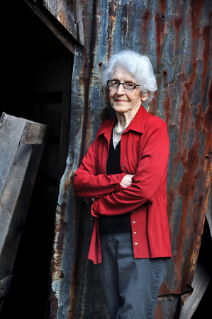 Elderly woman, ninety seven years old, poses by her old barn.  She is wearing glasses and a red jacket.  Her hair is white but her smile is still attractive.