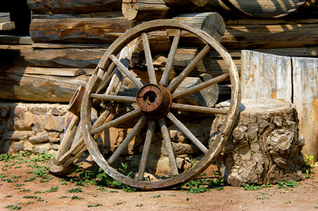 Old wagon wheel sits exposed to the weather against a log cabin.  All is wooden except for the metal bands and center hub.