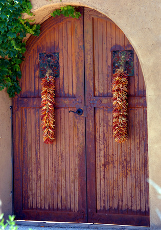 Rusty, Red Arched Door Is Set Into An Arched Adobe Door Frame. Red Chili