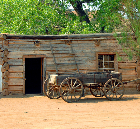Old wooden wagon is parked on a dusty lane outside of a log cabin. Wooden ladder leans against building.