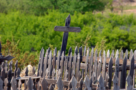 Weathered and broken, wooden crosses still stand in an old cemetery on the grounds of El Rancho del las Golondrinas near Santa Fe, New Mexico. Stock Photo