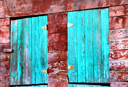 Old barn in New Mexico has turquoise doors and red faded walls.  Barn is weathered and paint is craked and peeling.