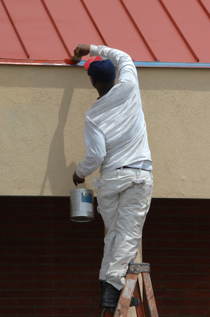 Painter, dressed in white, stands at the top of his ladder to reach the last big of trim that needs painting. Stok Fotoğraf